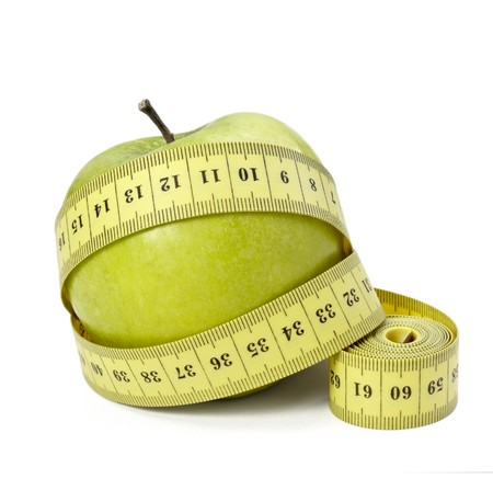 ailment: close up of measure tape and green apple on white background  Stock Photo