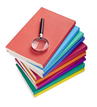 scientific literature: close up of colorful books  and magnifying glass on white background