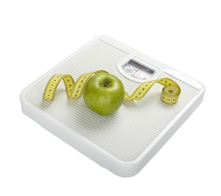 weighing: close up of scale, tape and apple on white background