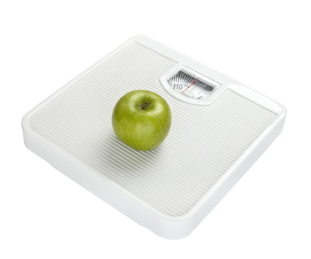 ailment: close up of scale and apple on white background