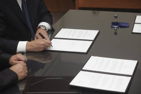 signing contract: close up of businessman hands signing contract Stock Photo
