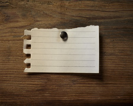 board pin: close up of grunge note paper on wooden background