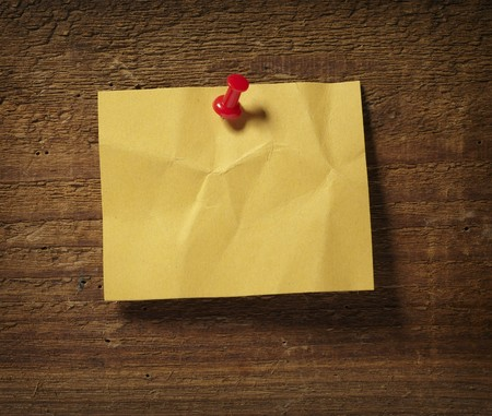noticeboard: close up of grunge note paper on wooden background