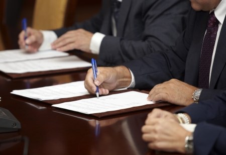 sign contract: close up of businessman hands signing contract Stock Photo