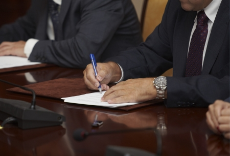 boardroom meeting: close up of businessman hands signing contract Stock Photo