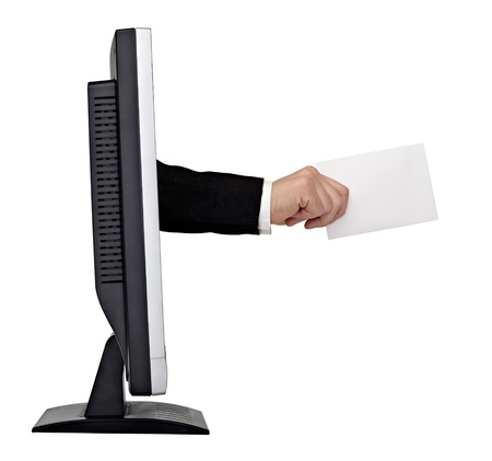 close up of a hand holding blank note reaching out of a computer screen on white background.