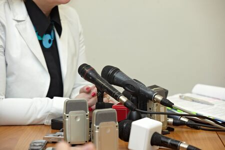 spokesman: close up of conference meeting microphones and businessman