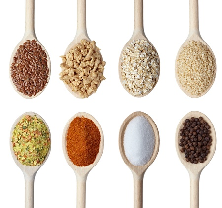 oatmeal: cerca de varios cereales y condimentos en cucharas de madera sobre fondo blanco. cada uno es asesinado por separado