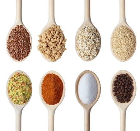 Cerca de varios cereales y condimentos en cucharas de madera sobre fondo blanco. cada uno recibe un disparo por separado Foto de archivo