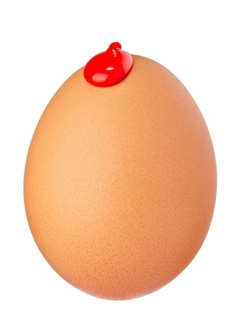 close up of an egg with leaking red paint on white background with clipping path photo
