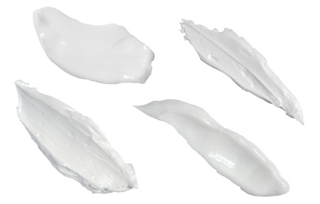 collection of various strokes of a white beauty cream on white background. each one is shot separately photo