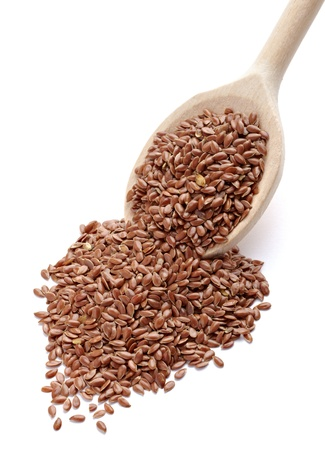 dietary fiber: close up of flax seeds in a wooden spoon on white background with clipping path