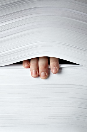 close up of businessman hand in stack of papers photo