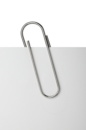 paper clip: close up of  a metal paper clip and paper on white background Stock Photo