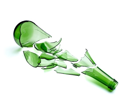 glass containers: close up of  a broken green bottle on white background