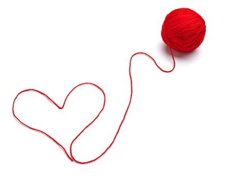 hilo rojo: cerca de una forma de bola y corazón de lana sobre fondo blanco