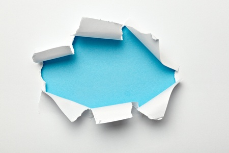 explode: close up of  a ripped paper hole on white background