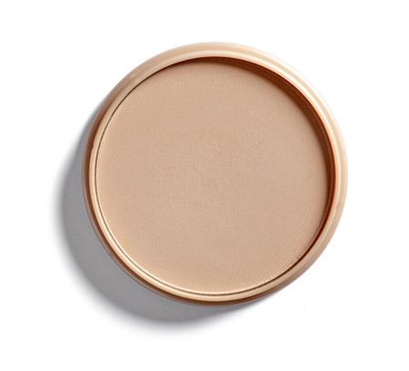 près d'un maquillage en poudre sur fond blanc