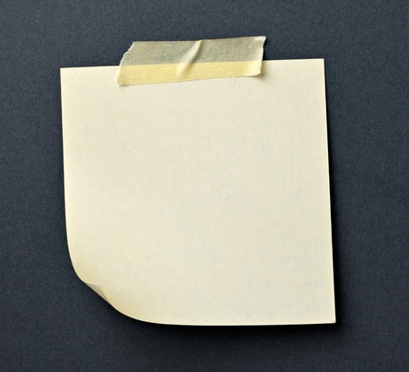 close up of note paper with adhesive tape on a gray background photo