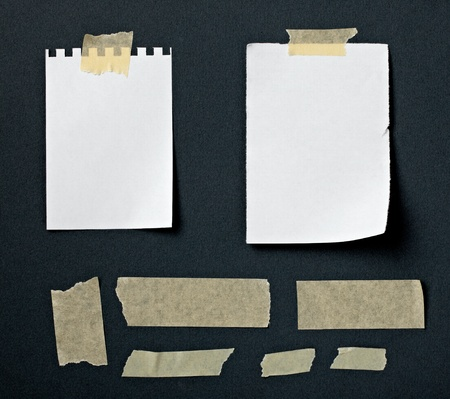 old notebook: close up of note paper with adhesive tape on a black background