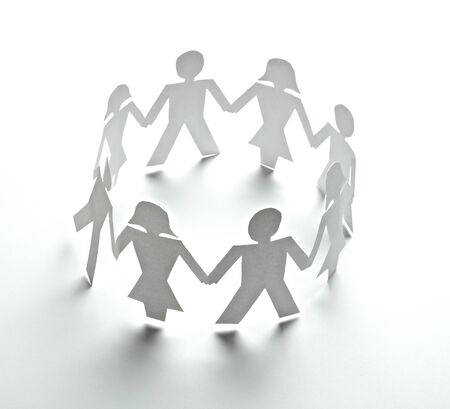 linked together: close up of  paper people on white background  Stock Photo