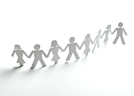 joined hands: close up of  paper people on white background  Stock Photo