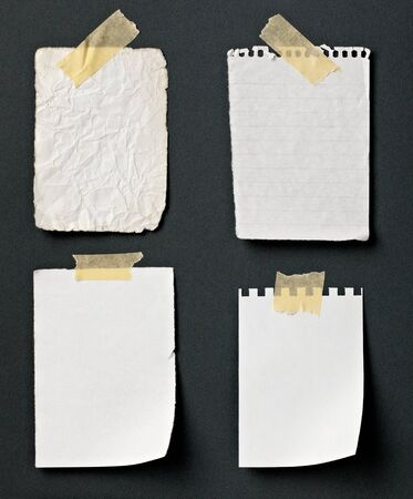 adhesive note: close up of note paper with adhesive tape on a black background