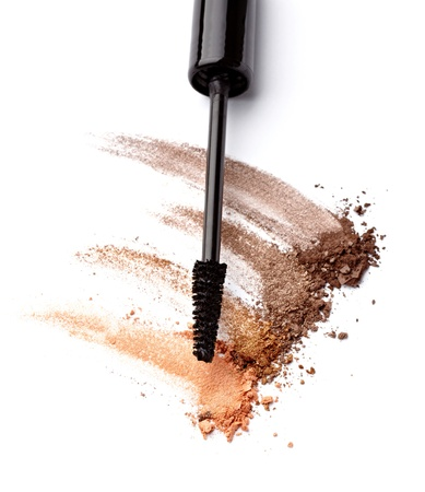 close up of black mascara and face powder on white background photo