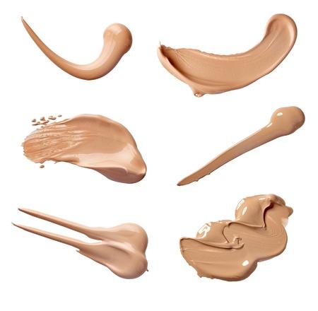 verzameling van verschillende make-up vloeibaar poeder slagen op een witte achtergrond. elk afzonderlijk wordt neergeschoten