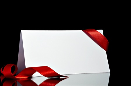 close up of  card note with  ribbon on black background  photo