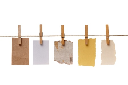 close up of  a notes and a clothes pegs on white background photo
