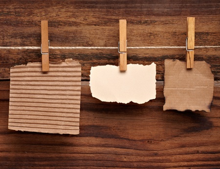 close up of  a note paper and clothes peg on a wooden background photo