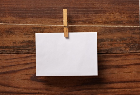 clothes pegs: close up of  a note paper and clothes peg on a wooden background Stock Photo