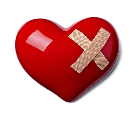 close up of a heart shape with bandage on white background photo