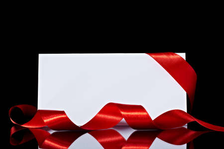 close up of  card note with ribbon on bright blurred lights background photo