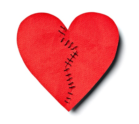 close up of  a stitched paper broken heart on white background with clipping path photo