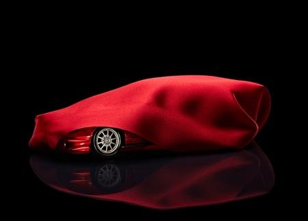 dream car: cerca de un coche nuevo oculta bajo la cubierta de color rojo sobre fondo negro Foto de archivo