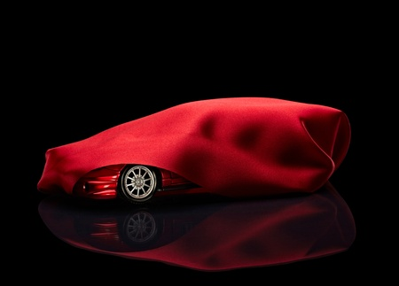 covering: close up of  a new car hidden under red cover on black background