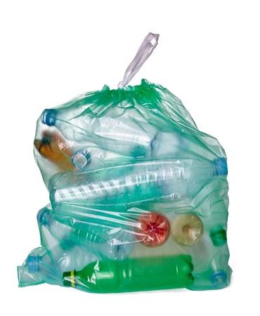 Close up di un sacco della spazzatura con bottiglie di plastica vuote su sfondo bianco