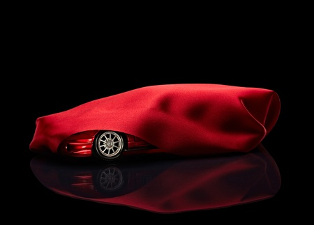 close up of  a new car hidden under red cover  photo