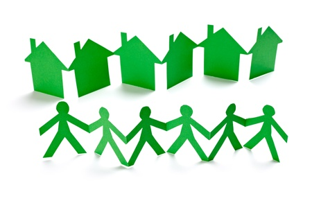 housing project: closeup of chain of paper people and houses cut on white background Stock Photo