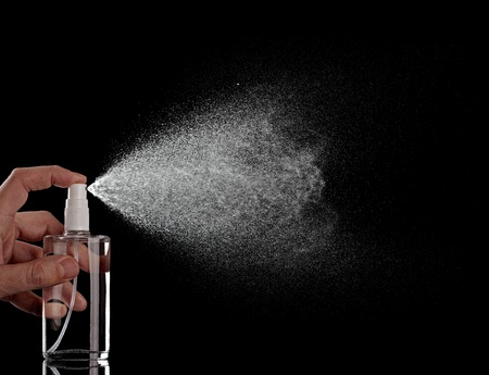 Nahaufnahme von einer Sprühflasche fällt auf schwarzem Hintergrund Standard-Bild