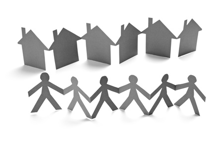 linked hands: closeup of chain of paper people and houses cut on white background Stock Photo