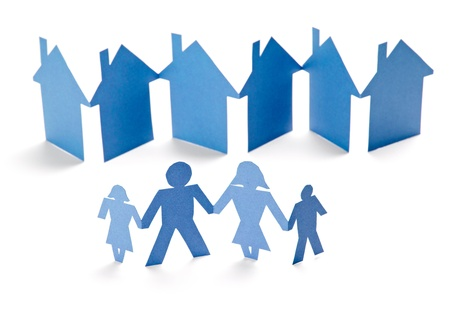 housing development: closeup of chain of paper people and houses cut on white background Stock Photo