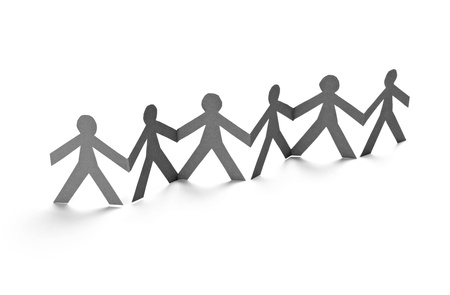 children holding hands: closeup of chain of paper people cut on white background