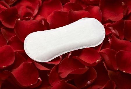 menses: close up of woman hygiene protection and rose petals on white background