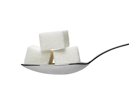 close up of  sugar cubes in a spoon on white background with clipping path photo