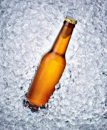 close up of a beer bottle in ice photo