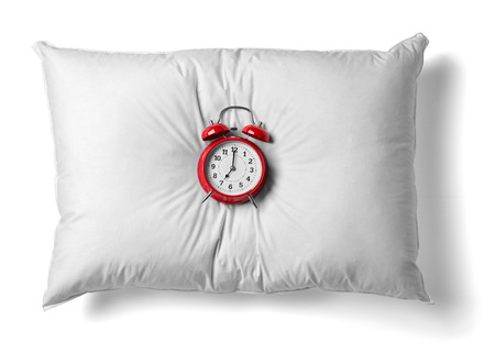 close up of  a white pillow and red alarm clockon white background
