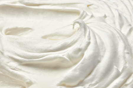 whip: close up of  a white whipped or sour cream on white background